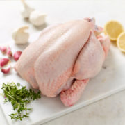 Organic whole chicken with lemon halves, garlic bulbs and segments and thyme