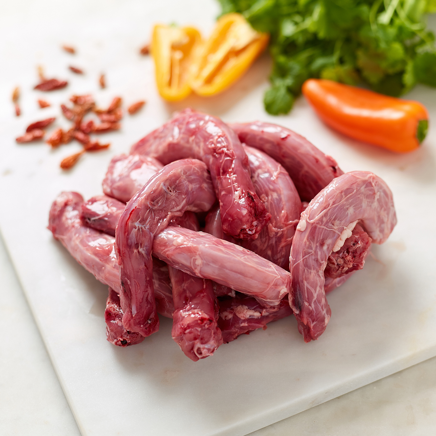 Organic Chicken Necks with birds eye chillies, whole and sliced peppers and coriander